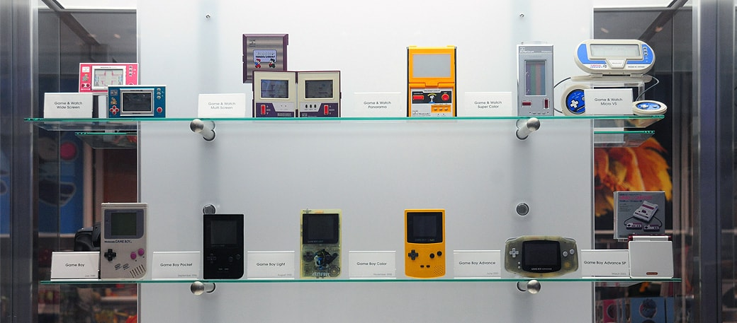 Display case with various Nintendo handheld systems.